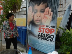 Gezaghèber Lydia Emerencia ku poster Stop Abuso - potrèt Belkis Osepa