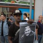 Un demonstradó ta mustra un potrèt di Mitch Henriquez durante un protesta na Den Haag – potrèt: Pieter Hofmann