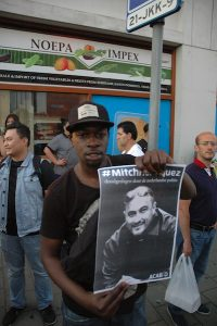 Un demonstrante ta mustra un potrèt di Mitch Henriquez durante un protesta na Den Haag na yüli 2015 –potrèt di archivo: Pieter Hofmann